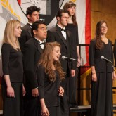 Members of the Buffalo State Chamber Choir performing on stage.