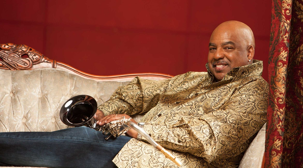 Gerald Albright posing with his saxophone on a couch.