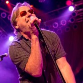 Southside Johnny singing into a microphone