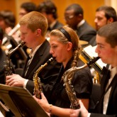 Three members of the Buffalo State Wind Ensemble playing the saxophone.