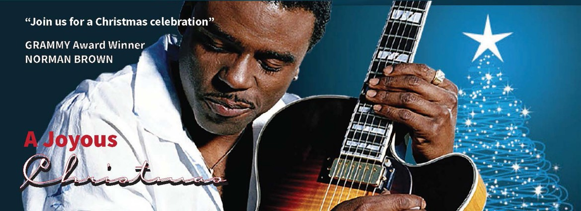 "A picture of Norman Brown holding his guitar stating that he is a Grammy award winner, the name of his tour (A Joyous Christmas) and ""Join us for a Christmas celebration."""