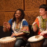 Two members of the West African Drumming Enemble playing the djembe